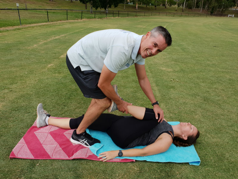 Personal Trainer stretching a client
